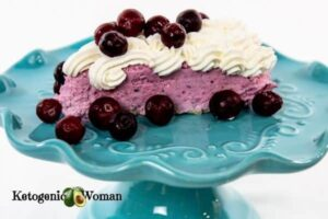 Cranberry mousse with whip cream on blue plate