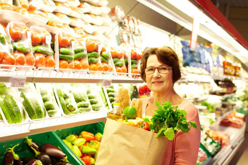 woman in grocery store holding bag of groceries