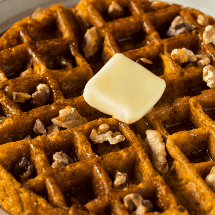 Keto Pumpkin Spice Waffles topped with butter and walnuts