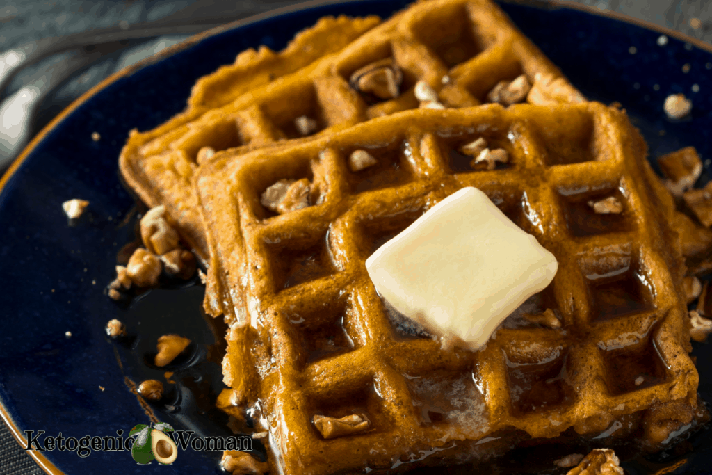 Pumpkin spice waffles with butter and nuts on blue plate