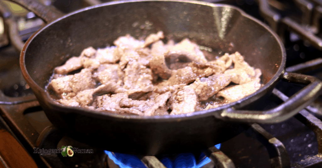 steak frying in cast iron pan over a flame